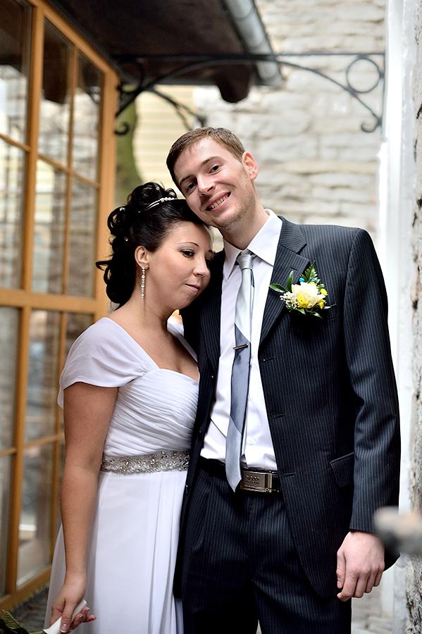 Нежные жених и невеста во время свадебной прогулки в Таллинне.